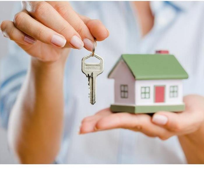 Person holding house in one hand and keys in the other